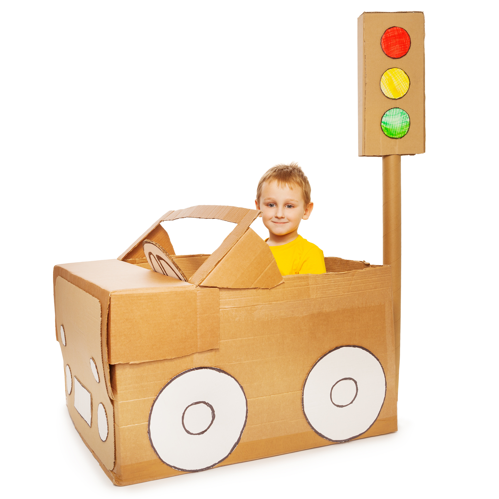 Little boy driving his handmade cardboard car, isolated on white background