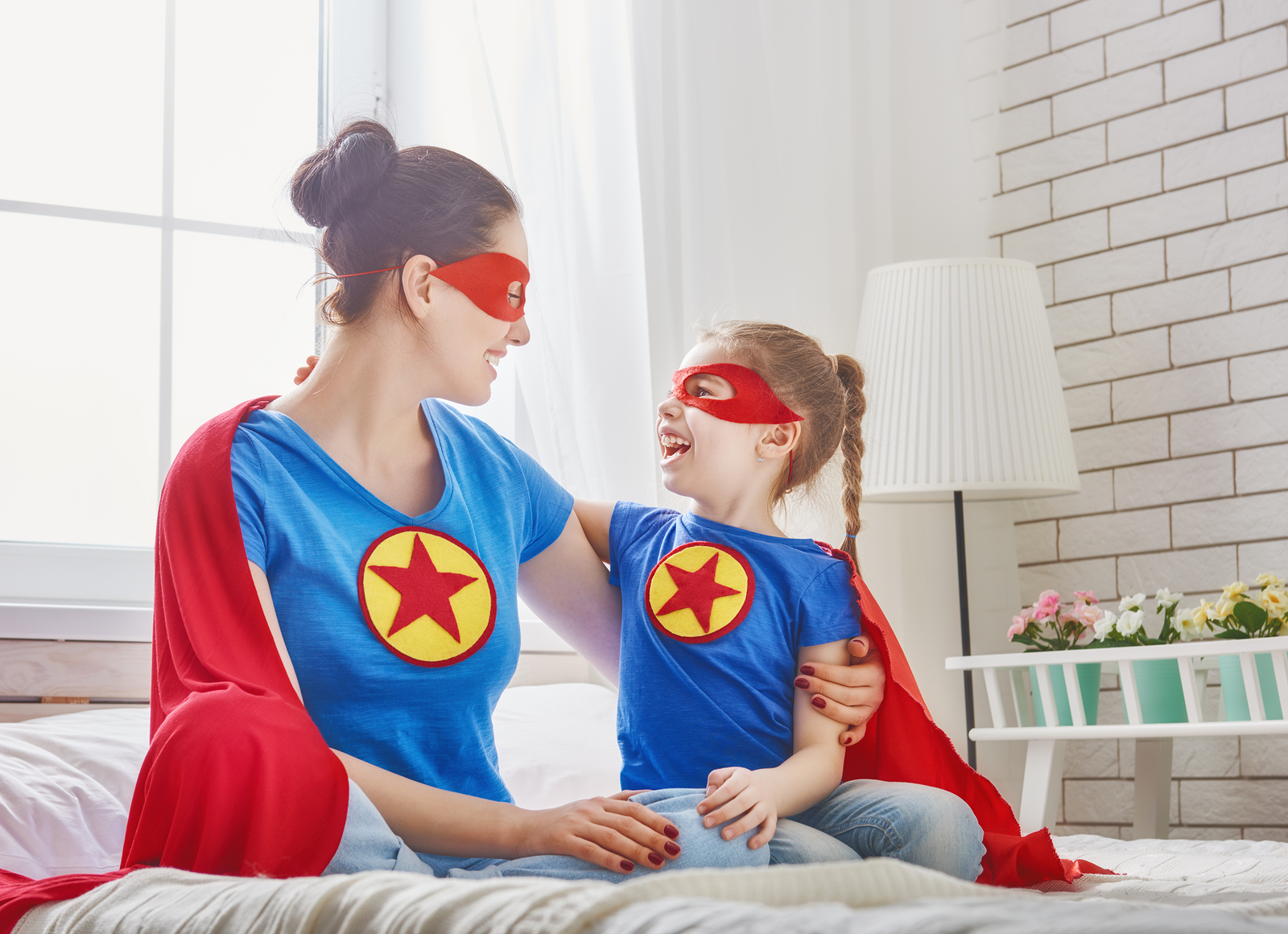 Mother and her child playing together. Girl and mom in Superhero