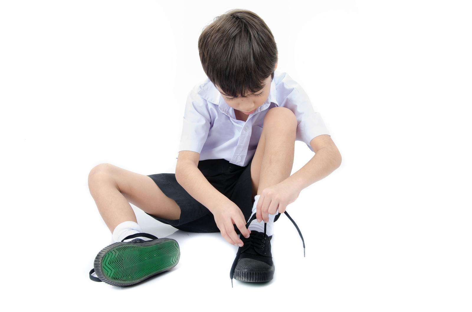 Little boy tie shoes ready for school on white background