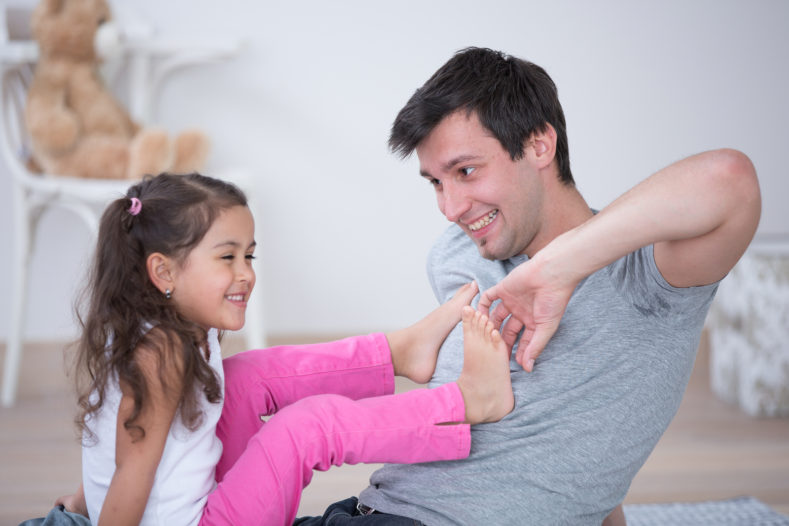 Father tickling daughter's foot at home